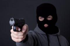 Άτομο στη μαύρη μάσκα που στοχεύει με το πυροβόλο όπλο πέρα από το γκρι Στοκ εικόνα με δικαίωμα ελεύθερης χρήσης
