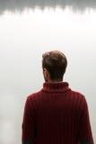 Άτομο στη σκούρο κόκκινο μπλούζα που εξετάζει τη λίμνη/τα σκεπτόμενα άτομα στο κόκκινο πουλόβερ που στέκεται με πίσω και που εξετ Στοκ Εικόνες