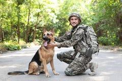 Άτομο στη στρατιωτική στολή με το γερμανικό σκυλί ποιμένων υπαίθρια Στοκ Εικόνα