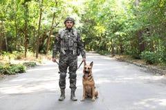 Άτομο στη στρατιωτική στολή με το γερμανικό σκυλί ποιμένων υπαίθρια Στοκ Φωτογραφίες