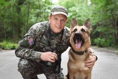 Άτομο στη στρατιωτική στολή με το γερμανικό σκυλί ποιμένων Στοκ Φωτογραφίες