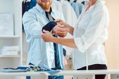 Άτομο στη συναρμολόγηση ενός επί παραγγελία πουκάμισου στο στούντιο του ράφτη στοκ φωτογραφία
