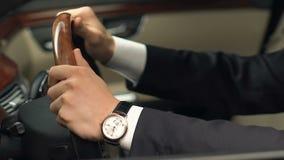 Άτομο στη συνεδρίαση κοστουμιών στη θέση οδηγών και το τιμόνι εκμετάλλευσης, νέα αγορά αυτοκινήτων απόθεμα βίντεο