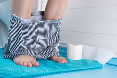 άτομο στη συνεδρίαση λουτρών στην τουαλέτα με το εσώρουχό του που αφαιρείται, δίπλα σε έναν ρόλο του χαρτιού τουαλέτας στοκ εικόνες με δικαίωμα ελεύθερης χρήσης