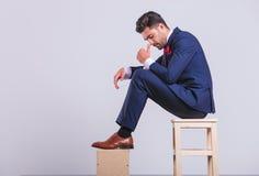 Άτομο στη συνεδρίαση κοστουμιών στο στούντιο που κοιτάζει κάτω ενώ σχετικά με τη μύτη Στοκ Εικόνες
