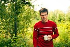 Νεαρός άνδρας στη φύση με μια κούπα του καφέ Στοκ Φωτογραφία