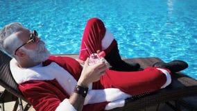 Άτομο στη χαλάρωση κοστουμιών Santa στο μόνιππο στη λίμνη φιλμ μικρού μήκους