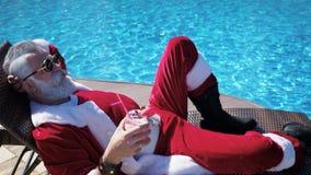 Άτομο στη χαλάρωση κοστουμιών Santa στο μόνιππο στη λίμνη απόθεμα βίντεο