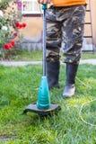 Άτομο στις λαστιχένιες μπότες με έναν θεριστή μπροστά από την πίσω αυλή Στοκ Φωτογραφίες