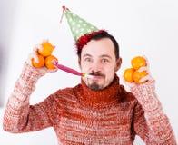 Άτομο στις διακοπές στο καπέλο και το συριγμό με tangerines Στοκ Φωτογραφία