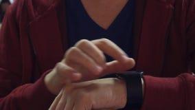 Άτομο στις κόκκινες βρύσες στο smartwatch του Σύγχρονη φορετή συσκευή 4K βίντεο κινηματογραφήσεων σε πρώτο πλάνο απόθεμα βίντεο