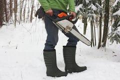 Άτομο στις μπότες και ένα αλυσιδοπρίονο στο δασικό, χαμηλότερο κορμό Στοκ Εικόνα