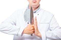 άτομο στον αρχιμάγειρα ομοιόμορφο με ένα αιχμηρό μαχαίρι στα χέρια του σε ένα λευκό Στοκ Εικόνες