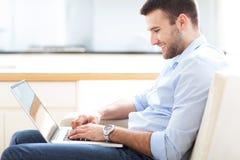 Άτομο στον καναπέ με το lap-top Στοκ εικόνες με δικαίωμα ελεύθερης χρήσης