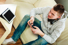 Άτομο στον καναπέ με το smartphone και την ταμπλέτα ακουστικών Στοκ φωτογραφία με δικαίωμα ελεύθερης χρήσης