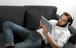 Άτομο στον καναπέ στο ακουστικό Στοκ Εικόνες