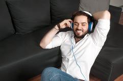 Άτομο στον καναπέ στο ακουστικό Στοκ εικόνες με δικαίωμα ελεύθερης χρήσης