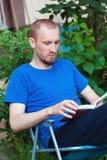 Άτομο στον καφέ κατανάλωσης κατωφλιών και ανάγνωση του βιβλίου Στοκ Φωτογραφίες