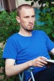 Άτομο στον καφέ κατανάλωσης κατωφλιών και ανάγνωση του βιβλίου Στοκ Εικόνες