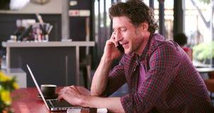 Άτομο στον καφέ που λειτουργεί στο lap-top και που απαντά στο τηλέφωνο απόθεμα βίντεο