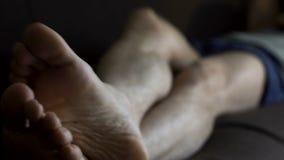 Άτομο στους μπόξερ που κοιμούνται στον καναπέ και τα γρατσουνίζοντας πόδια, τα προβλήματα δερμάτων και την υγεία απόθεμα βίντεο