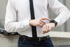 Άτομο στο άσπρους πουκάμισο και το δεσμό, που δείχνουν το δάχτυλο στο έξυπνο ρολόι Στοκ Φωτογραφίες