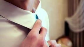 Άτομο στο άσπρο πουκάμισο που δένει έναν δεσμό κοντά στο παράθυρο απόθεμα βίντεο