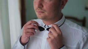 Άτομο στο άσπρο πουκάμισο που δένει έναν δεσμό κοντά στο παράθυρο φιλμ μικρού μήκους