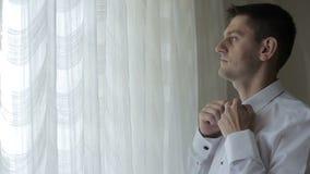 Άτομο στο άσπρο πουκάμισο που δένει έναν δεσμό τόξων κοντά στο παράθυρο απόθεμα βίντεο