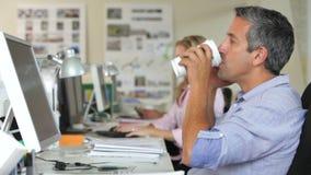 Άτομο στο γραφείο με τον κινητό καφέ τηλεφωνικής κατανάλωσης φιλμ μικρού μήκους