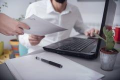 Άτομο στο γραφείο που δίνει το έγγραφο Στοκ φωτογραφία με δικαίωμα ελεύθερης χρήσης