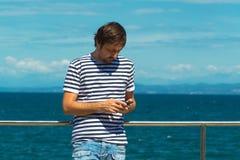 Άτομο στο γδυμένο πουκάμισο ναυτικών που στέλνει SMS θαλασσίως Στοκ Φωτογραφία