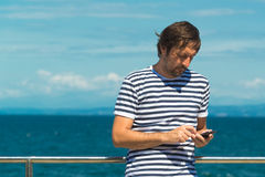 Άτομο στο γδυμένο πουκάμισο ναυτικών που στέλνει SMS θαλασσίως Στοκ Εικόνα