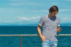 Άτομο στο γδυμένο πουκάμισο ναυτικών που στέλνει SMS θαλασσίως Στοκ εικόνα με δικαίωμα ελεύθερης χρήσης
