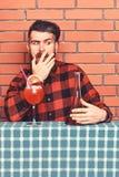Άτομο στο ελεγμένο πουκάμισο κοντά στο μπουκάλι, το τουβλότοιχο και το μπλε υπόβαθρο τραπεζομάντιλων Ο μπάρμαν με τη γενειάδα στο στοκ εικόνες