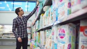 Άτομο στο εμπορικό κέντρο που επιλέγει τα προϊόντα για τις πάνες παιδιών απόθεμα βίντεο