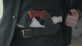 Άτομο στο επίσημο κοστούμι και ένα πυροβόλο όπλο στενό σε επάνω ζωνών του απόθεμα βίντεο