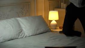 Άτομο στο επιχειρησιακό κοστούμι που έρχεται στο δωμάτιο ξενοδοχείου που πίνεται, πέφτοντας στο κρεβάτι, αλκοολισμός απόθεμα βίντεο
