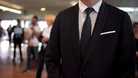 Άτομο στο επιχειρησιακό κοστούμι που περιμένει τις αφίξεις στην αίθουσα αερολιμένων, ταξιδιωτικός πράκτορας, τουρισμός στοκ εικόνες