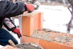 Άτομο στο εργοτάξιο οικοδομής που λειτουργεί με τα τούβλα και το κονίαμα, τοίχοι σπιτιών οικοδόμησης Στοκ φωτογραφία με δικαίωμα ελεύθερης χρήσης