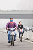 Άτομο στο ε-ποδήλατο καλμένη στην αιθαλομίχλη πόλη, Πεκίνο, Κίνα στοκ εικόνες