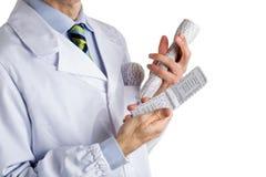Άτομο στο ιατρικό παλτό που κρατά την τρισδιάστατη τυπωμένη ύλη lightbulb, φακός, phon Στοκ εικόνες με δικαίωμα ελεύθερης χρήσης