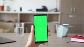 Άτομο στο καθιστικό που κρατά ένα smartphone με την πράσινη χλεύη χρώματος οθόνης επάνω φιλμ μικρού μήκους
