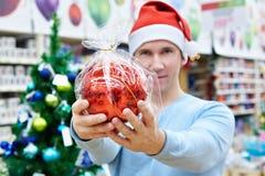 Άτομο στο καπέλο Santa που κρατά το κόκκινο χριστουγεννιάτικο δέντρο σφαιρών Στοκ εικόνες με δικαίωμα ελεύθερης χρήσης