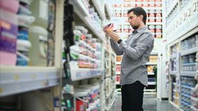 Άτομο στο κατάστημα χρωστικών ουσιών Σειρές των ραφιών με τα δοχεία χρωμάτων