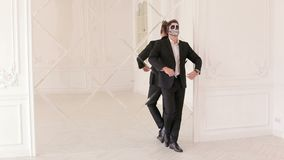 Άτομο στο κοστούμι με τη σύνθεση κρανίων αποκριών, στέκεται στον τοίχο καθρεφτών απόθεμα βίντεο
