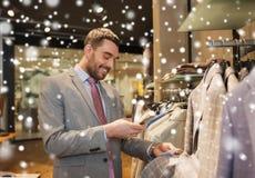 Άτομο στο κοστούμι με το smartphone στο κατάστημα ιματισμού Στοκ φωτογραφία με δικαίωμα ελεύθερης χρήσης