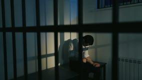 Άτομο στο κοστούμι πίσω από τους φραγμούς φυλακών απόθεμα βίντεο