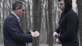 Άτομο στο κοστούμι που αγοράζει ένα πυροβόλο όπλο για τα χρήματα Δόσιμο bancnotes στον έμπορο Παράνομη συναλλαγή όπλων απόθεμα βίντεο