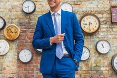 Άτομο στο κοστούμι που στέκεται κοντά στον τοίχο με τα ρολόγια στοκ φωτογραφία με δικαίωμα ελεύθερης χρήσης